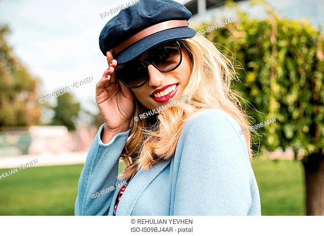 Portrait of woman wearing sunglasses and baker boy cap looking at camera smiling