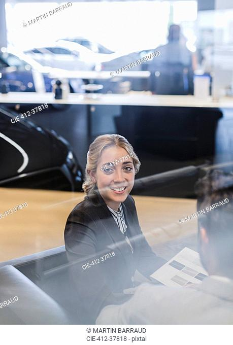 Portrait smiling car saleswoman working in car dealership showroom