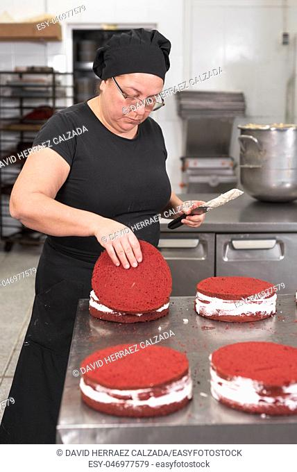 Woman pastry chef smiling and working happy, making cakes at the pastry shop