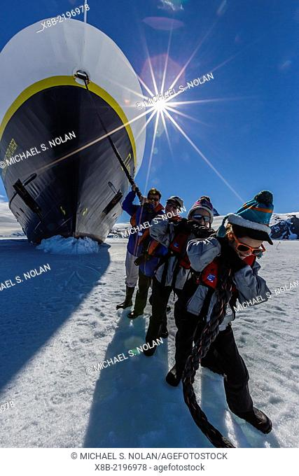 """Family members """"""""hauling"""""""" the National Geographic Explorer on first year sea ice in Duse Bay, Erebus and Terror Gulf, Weddell Sea, Antarctica"""