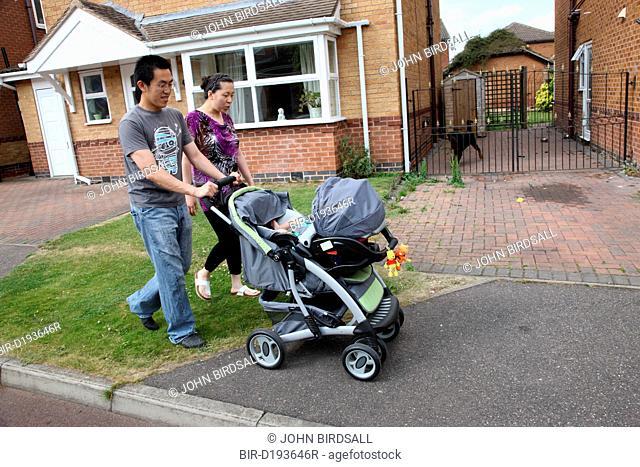 Chinese parents walking down street with pram