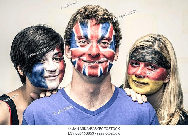 Portrait of young smiling people with painted European flags on their faces