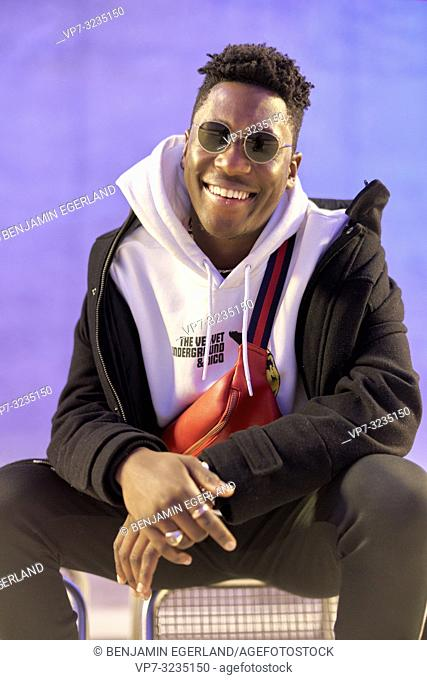 young happy man with a big toothy smile, purple background, in Munich, Germany