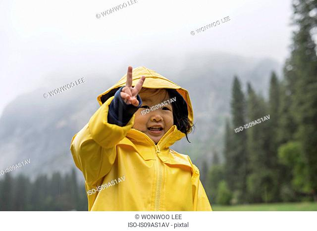 Portrait of female toddler wearing yellow raincoat making peace sign, Yosemite National Park, California, USA