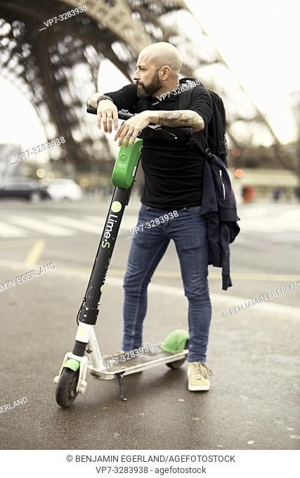 man on electric scooter in Paris, France