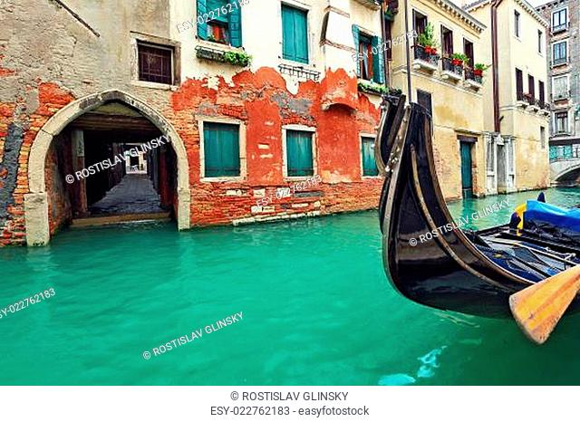 Gondola on canal in front of typical old brick house in Venice, Italy