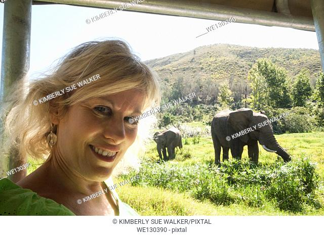 Blond woman on jeep safari with elephants in view, Mosselbay, Western Cape, South Africa