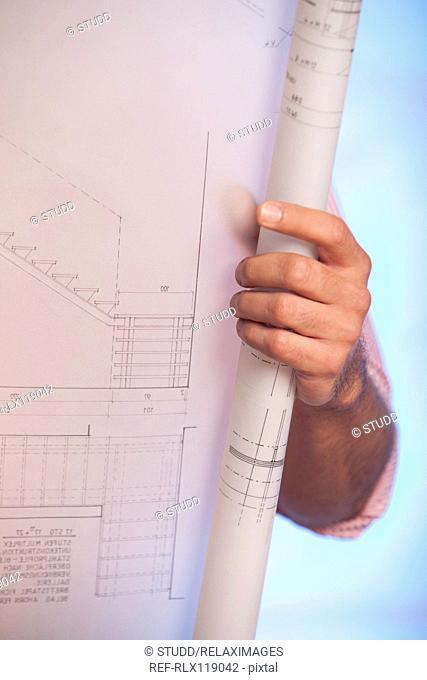 Man holding blueprint architectural drawing plan