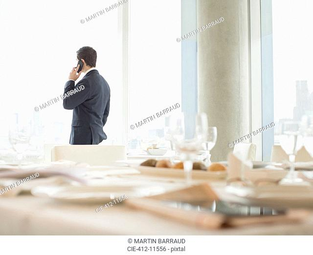 Businessman talking on cell phone in restaurant