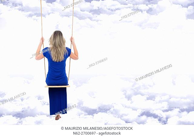 Relaxed blonde woman, rear view, dressed in a long blue dress on the swing, suspended through the clouds of a fantasy blue sky