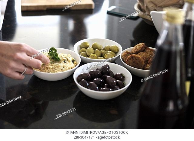Hummus classic,black and green olives and falafel,Group of friends casually snacking on a selection of food while laughing and enjoying themselves