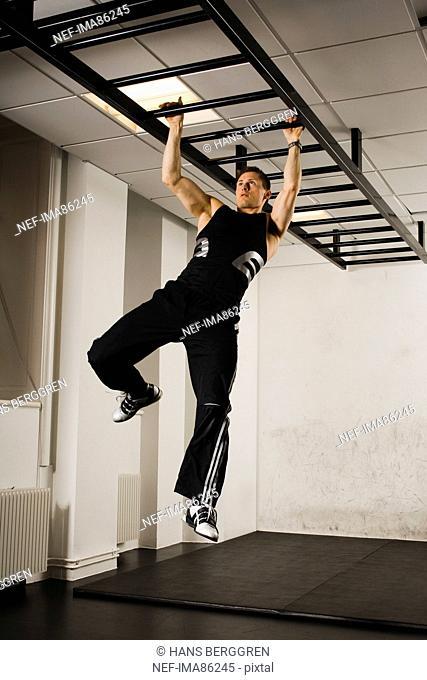 Male athlete using gymnastics equipment in gym