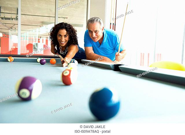 Senior man and wife playing on pool table