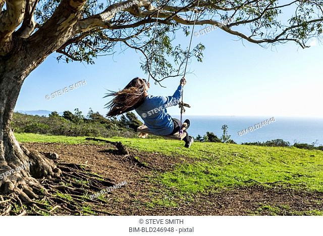Caucasian woman on tree swing near ocean