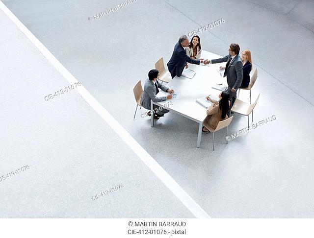 Businessmen in meeting shaking hands across table
