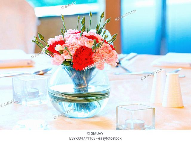 Close up red and orange color carnation flower bouquet in old glass vase on dinning table