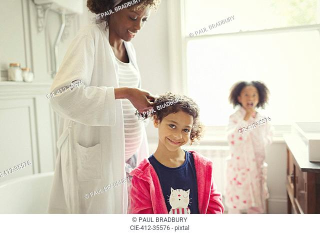 Pregnant mother fixing daughter hair in bathroom