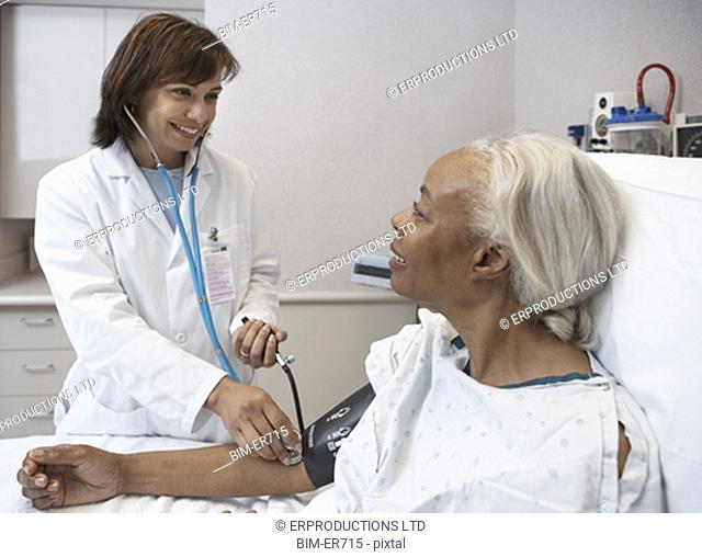African female doctor taking senior patientÆs blood pressure