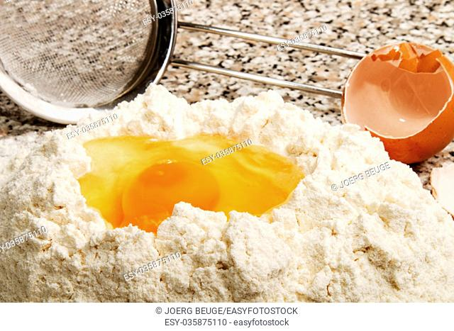 freshly opened egg in flour and egg shell in the background
