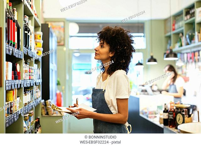 Woman with clipboard at shelf in a store