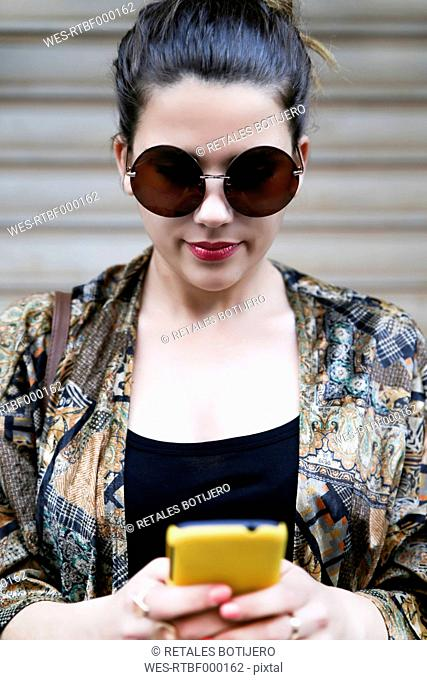 Portrait of young woman wearing sunglasses looking at smartphone