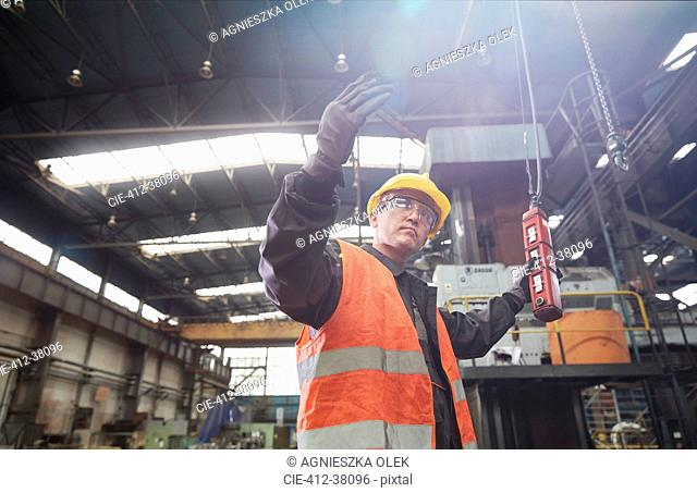 Male worker operating machinery at control panel, gesturing