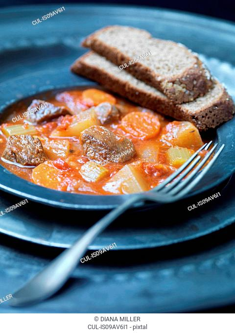 Plate of navarin of lamb with carrots, celery, tomatoes and wholegrain bread