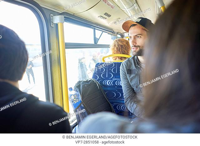 attentive young man with cap sitting in public transport with friends in Malta, Europe