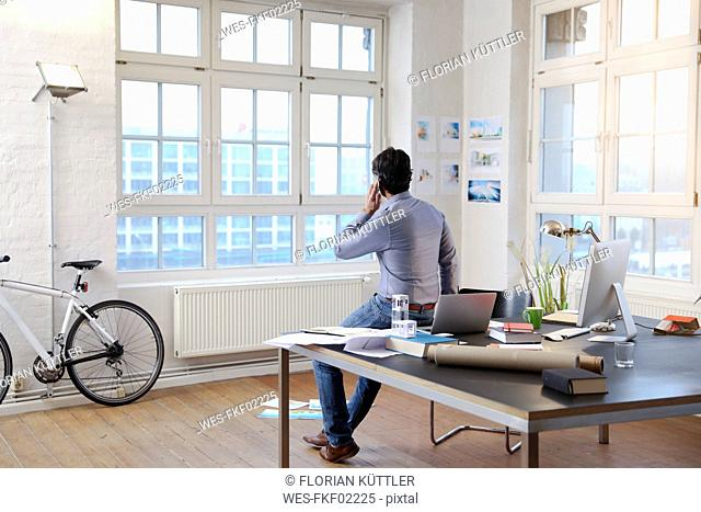 Man using cell phone in a modern informal office