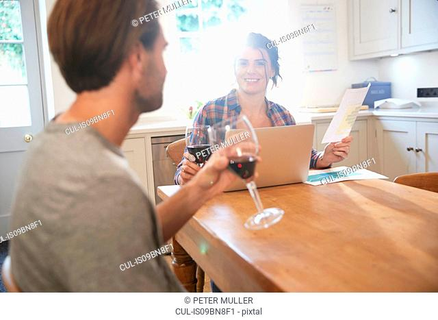 Couple at kitchen table drinking red wine while doing paperwork