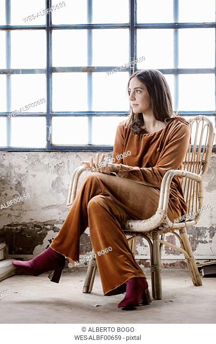 Fashionable young woman sitting on basket-chair in a loft