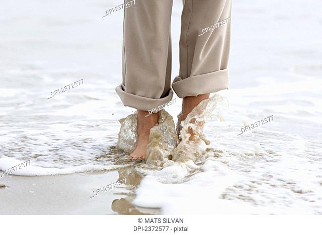 Walking Barefoot Along The Beach With Water Washing Over Feet; Rimini, Emilia-Romagna, Italy