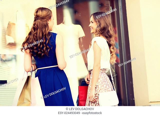 sale, consumerism and people concept - happy young women with shopping bags talking at to shop window in city from back