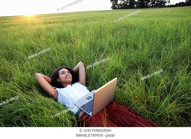African woman laying in meadow with laptop