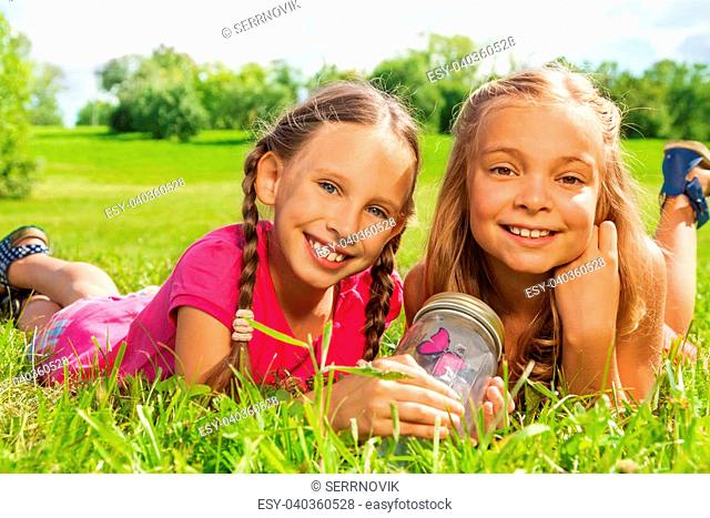 6029c6f733 Close-up of two happy little nine years old girls hold jar with butterfly  laying