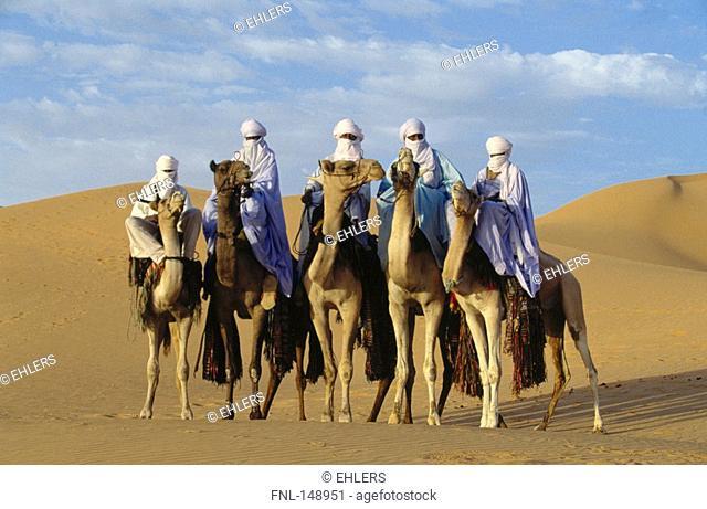 Five tuareg riders on camels, Sahara Tekerkiba, Lybia