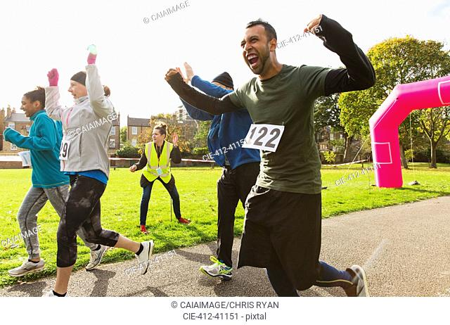 Exuberant male runner cheering at charity run in sunny park