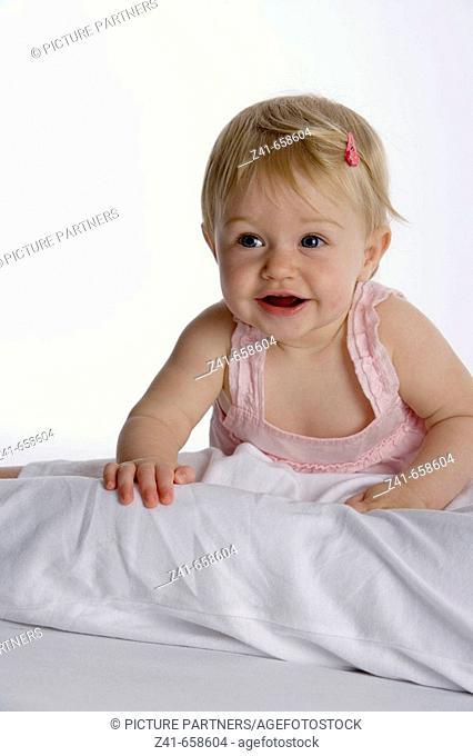 Blond little girl climbing on her mothers legs