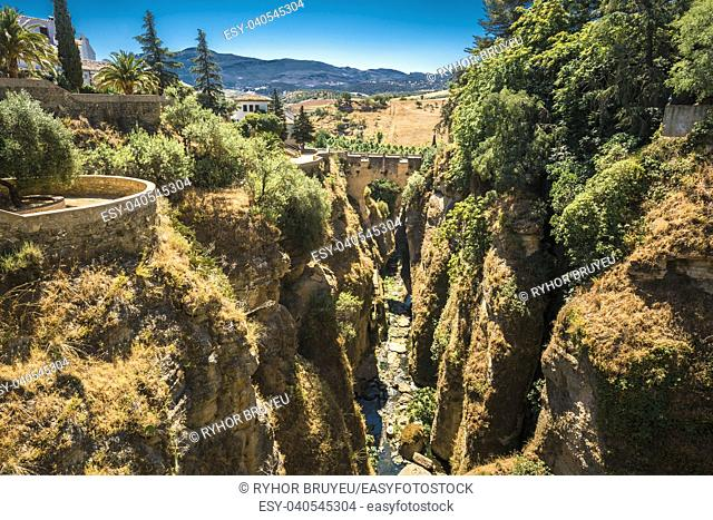 The Puente Viejo (Old Bridge) is oldest and smallest of three bridges that span the 120-metre deep chasm that carries Guadalevin River and divides city of Ronda