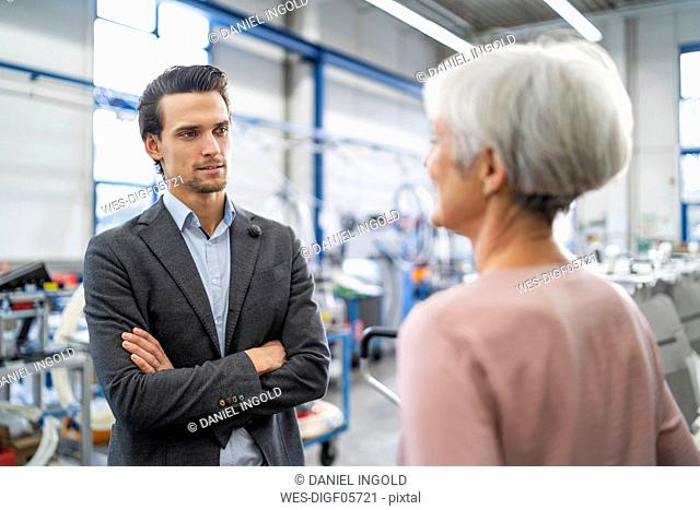 Smiling businessman and senior businesswoman talking in a factory