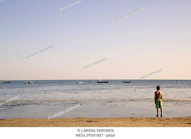 Italy, Gorizia, Grado, boy standing at seafront looking at horizon