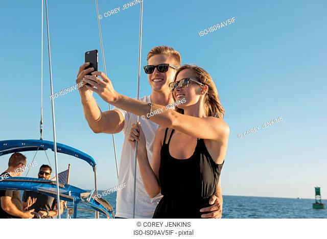 Couple taking selfie on sailboat, San Diego Bay, California, USA