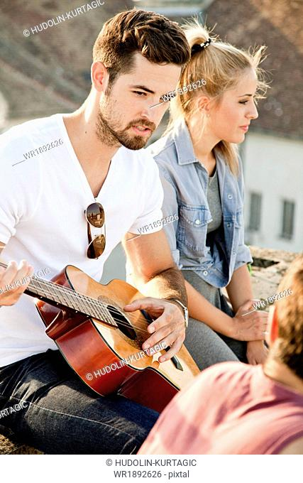 Young man playing guitar at rooftop party