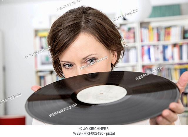 Woman at home loooking at record