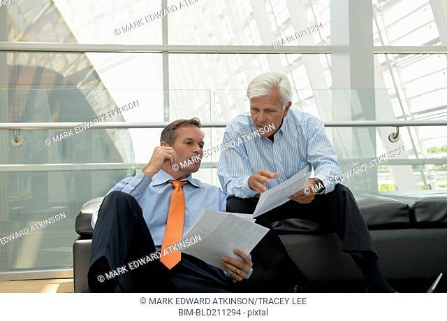 Caucasian businessmen talking in lobby area