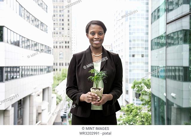 A businesswoman holding a small plant while standing next to a large convention centre window