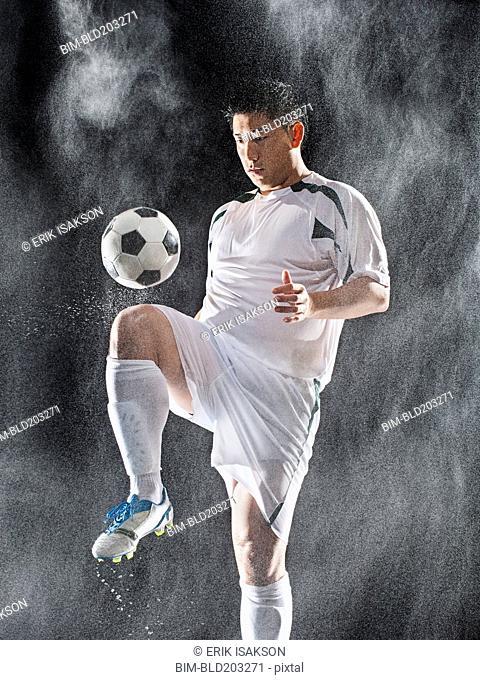 Asian soccer player kicking ball in rain