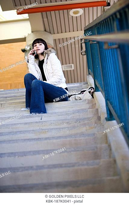 Portrait of a young woman sitting at the top of a concrete staircase on cellphone
