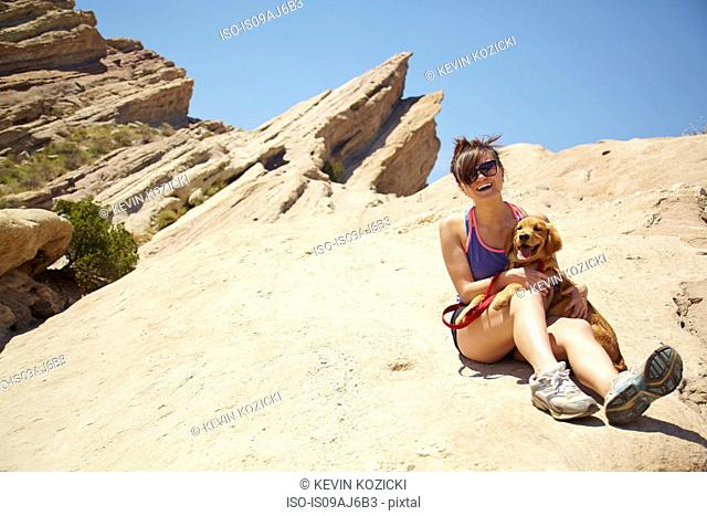 Young woman with labrador puppy sitting on lap