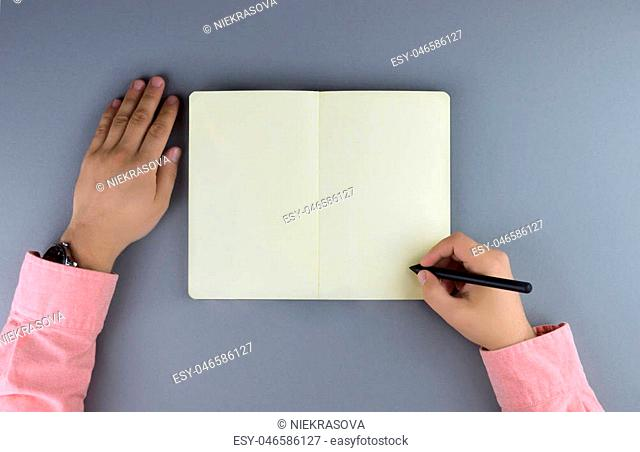 Hands writing in the note book. Flat lay style